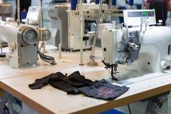 Швейная машина и ткань в магазине вырезывания, никто стоковые фото