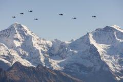 Швейцарская военновоздушная сила летает со своими вертолетами дисплей в горах стоковые фото