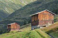 Швейцарские сеновалы на высокогорных лугах Стоковая Фотография RF