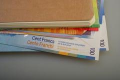 Швейцарские счеты бумаги наличных денег лежат на блокноте Стоковая Фотография RF