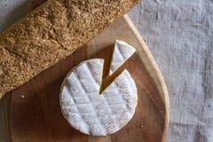 Швейцарский камамбер сформировал сыр и триангулярную часть сыра на деревянной текстурированной доске и багета зерна на сплетенном Стоковые Изображения