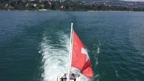 Швейцарский флаг развевая на задней части шлюпки скорости выходя порт Лозанны на озеро Leman Женева озера, Швейцарию видеоматериал