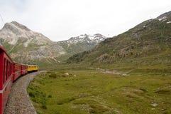 Швейцарское срочное Bernina поезда горы пересеченное через высокий mo Стоковая Фотография RF