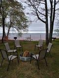 Швырок пикника ослабляет ветви ствола дерева березы горизонта воды озера песчаный пляж ямы огня стульев белые стоковая фотография rf