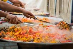 Шевелить варить ингридиенты в больших сковородах Гигантская паэлья Стоковые Изображения