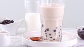 Шевелить вкусный тайваньский популярный чай молока пузыря жемчуга тапиоки напитка в стеклянной чашке на подносе яркой мраморной т сток-видео
