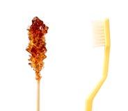 Шевелилка желтого сахарного песка против зубной щетки Стоковые Фотографии RF