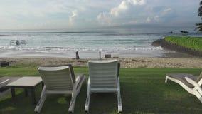 Шезлонги на банке пустого тропического пляжа во время низкого сезона На сильном ветере моря и больной волне, Солнце в небе i акции видеоматериалы