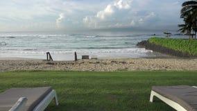 Шезлонги на банке пустого тропического пляжа во время низкого сезона На сильном ветере моря и больной волне, Солнце в небе i видеоматериал