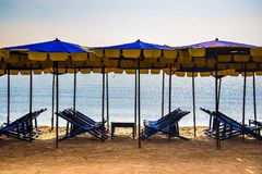 Шезлонги на песке смололи с зонтиками в сезоне лета Стоковые Изображения RF