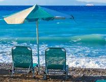 2 шезлонги и зонтика на береге pebbly пляжа Греции Родоса Стоковое фото RF