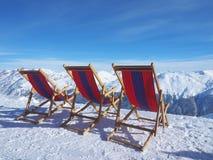 Шезлонги перед наклонами лыжи в горы горных вершин Стоковое Фото