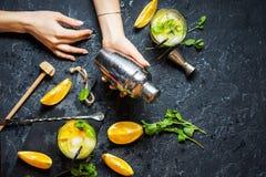 Шейкер владением руки женщины Холодный спиртной коктеиль цитруса лета с апельсином и мятой в стеклах и на темной каменной предпос Стоковые Изображения RF
