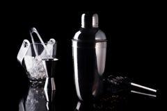 Шейкер коктеиля, swizzle, схваты и ложка с льдом в ведре для подготавливать напиток коктеиля лета на черной таблице Стоковая Фотография RF