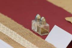 Шейкер соли и перца сервировки стола свадьбы с картой места стоковые фотографии rf