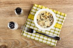 Шейкер соли и шейкер перца, julienne с цыпленком, грибом в шаре, вилке на салфетке на таблице r стоковые фотографии rf