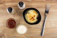 Шейкер соли, шейкер перца, кетчуп и майонез, julienne с цыпленком, грибом в черном шаре, вилке на таблице r стоковые изображения