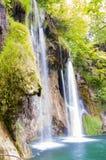 Шелковистые потоки водопада окруженные лесом в озерах национальном парке Plitvice, Хорватии Стоковые Фото