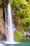 Шелковистые потоки водопада окруженные лесом в озерах национальном парке Plitvice, Хорватии Стоковая Фотография