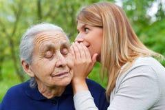 Шептать секрету к grandma& x27; ухо s Стоковые Фотографии RF