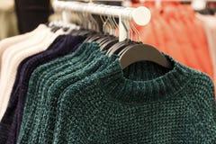 Шерстяные связанные свитеры вися на вешалках в магазине, конце-вверх стоковые фотографии rf