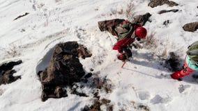 Шестерня 2 альпинистов полностью, со шлемами и рюкзаками, преодолевающ глубокие сугробы и скользкие утесы, подъем к верхней части сток-видео
