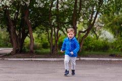 Шестилетний кавказский мальчик в голубом windbreaker и серых брюках бежать в парке стоковое изображение