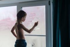 Шестилетний мальчик нося джинсы рисует шлюпку на туманном окне стоя на windowsill дома стоковое фото