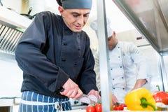 Шеф-повара варя и режа овощи и томаты Стоковая Фотография