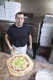 шеф-повара взятие пиццы вне Стоковые Фото