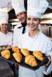 3 шеф-повара держа поднос испеченных круассана и печений Стоковые Фотографии RF
