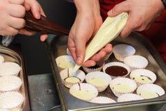 2 шеф-повара заполняют бумажные сыр горгонзоли форм и шоколад и делать флан горячего шоколада Стоковое Изображение