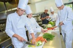 Шеф-повара команды подготавливая овощи Стоковые Изображения