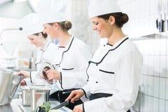 Шеф-повара подготавливая еды в коммерчески кухне Стоковые Фотографии RF