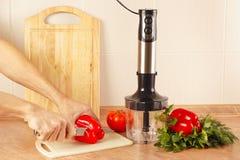 Шеф-повара рук отрезали красное bellpepper на кухонном столе Стоковое Изображение