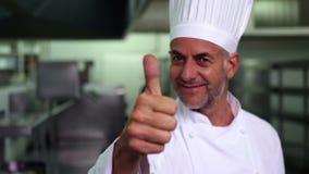 Шеф-повар давая большие пальцы руки вверх и усмехаясь на камере сток-видео