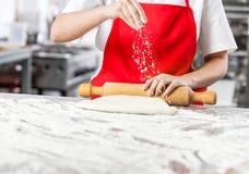 Шеф-повар брызгая муку пока свертывающ тесто на грязном Стоковые Изображения