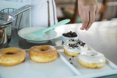 Шеф-повар брызгая над donuts стоковая фотография rf
