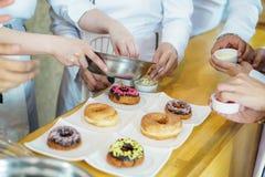 Шеф-повар брызгая donuts с сахаром стоковые изображения rf