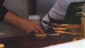Шеф-повар варит на блинчиках плиты видеоматериал