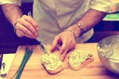 Шеф-повар варит bruschettas при тонизированный соус авокадоа, Стоковое фото RF