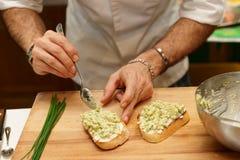 Шеф-повар варит bruschettas с соусом авокадоа Стоковые Изображения RF