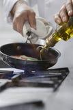 Шеф-повар варя еду в сковороде Стоковое Изображение