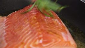 Шеф-повар варя и spicing рыб семг с рисом и огурцом видеоматериал