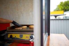 Шеф-повар варя котлету и плюшку на гриле для совершенного бургера в тележке улицы Стоковые Изображения