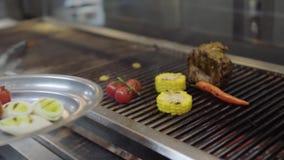 Шеф-повар варя овощ на гриле в конце-вверх кухни ресторана Сварите установку на мясо плиты, мозоль, вишню акции видеоматериалы