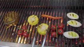 Шеф-повар варя овощ на гриле в конце-вверх кухни ресторана Сварите жарить мясо, мозоль, томаты вишни сток-видео