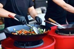 Шеф-повар варя тайский крупный план блюда на фестивале еды улицы стоковое фото rf