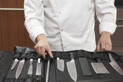 Шеф-повар выбирая заточник ножа из полного комплекта Стоковые Изображения