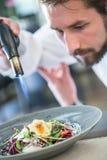 Шеф-повар в кухне гостиницы или ресторана жарит козий сыр стоковые изображения rf